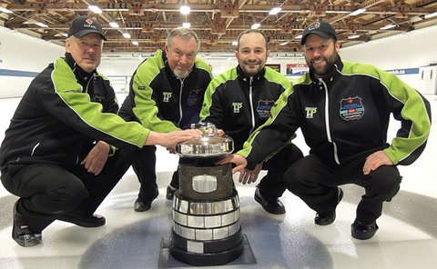 Four men in same uniform crouch and hold onto a trophy on a curling sheet