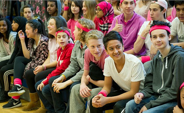 Students wearing some form of pink clothes sitting on bleachers.