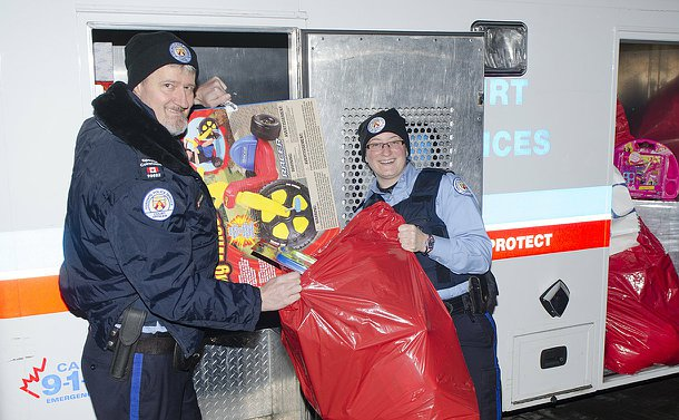 A man and woman in Toronto Police court officer uniforms unload toys from a prisoner transportation wagon