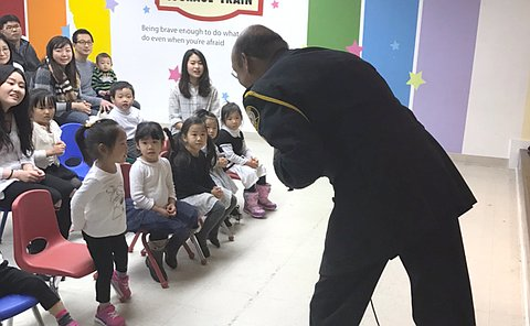 A girl talks to a man in TPS uniform who leans toward her