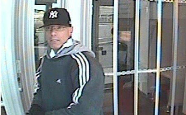 A man in a baseball cap near a bank machine
