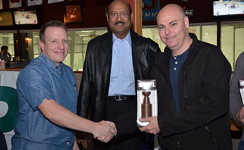 A man shakes hands with another man and hands him a gift alongside another man looking at the camera