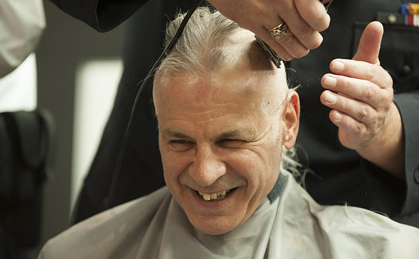 A man has his head shaved