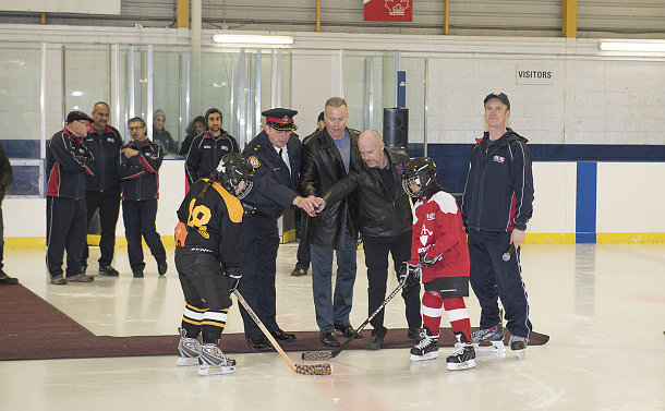 Four men standing at centre ice as two kids wait of puck to drop