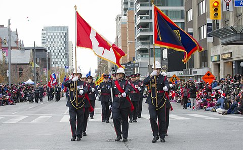 A large group of men and women in uniform, the front group with Canada and Toronto Police flags