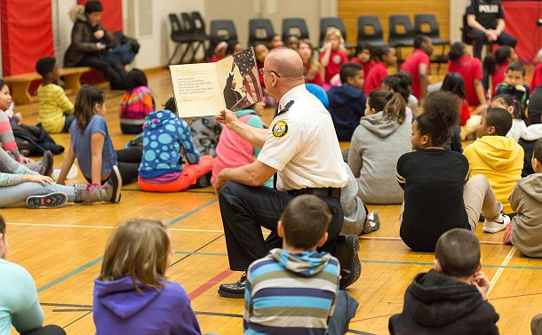 A man in TPS uniform holds a book amid a group of seated boys and girls in a gym