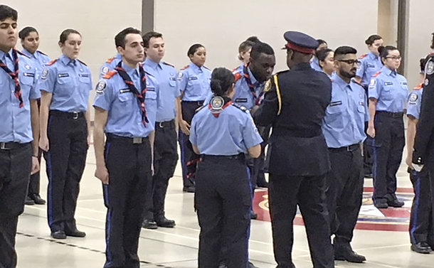 A man in TPS uniform puts a neckerchief on a young man in scouting uniform