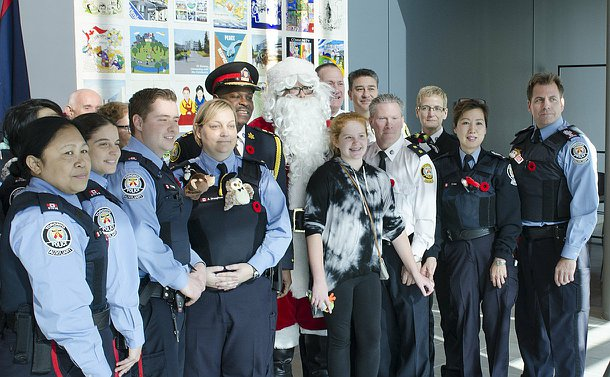 A group of men and women in TPS uniform, a girl and a man in a Santa costume