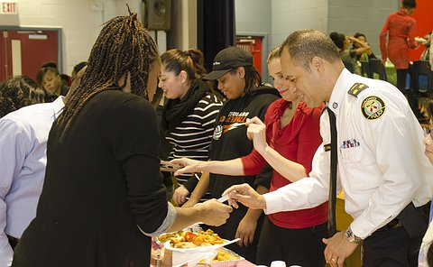 A man in TPS uniform with a group of people at a buffet table