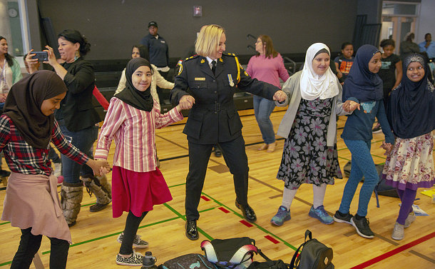 Woman dressed in a police uniform dances with students during a ceremony
