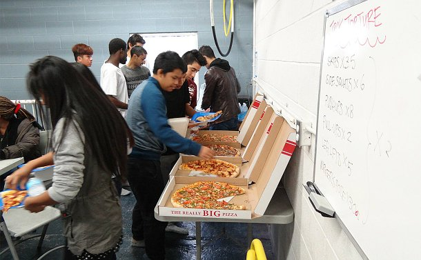 People taking pizza from boxes