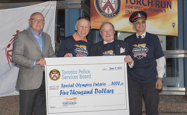 Four men holding a large cheque