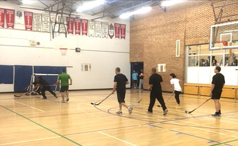 People playing floor hockey in a gym