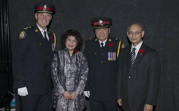 The police of chief posing with a man in uniform, a woman and the Chair of the police board.