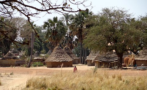 A man kneels of the ground in front of a small village of homes with peaked thatched roofs