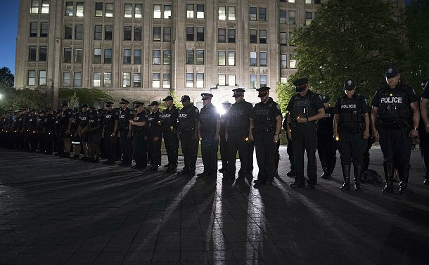 Men and women in TPS uniform bow heads