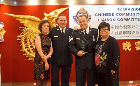 Two men in TPS uniform stand with two women