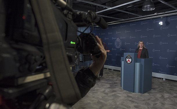 A woman stands at a podium with a video camera in foreground