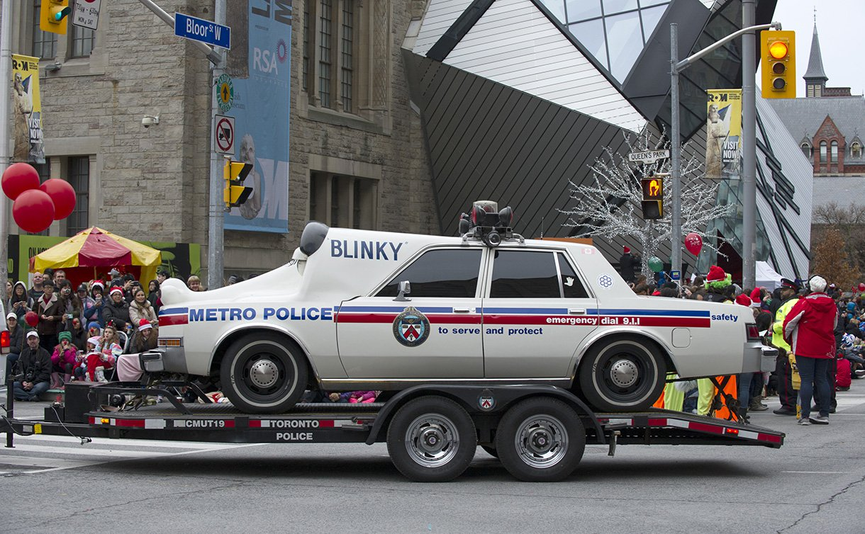 A modified police car being towed on a trailer