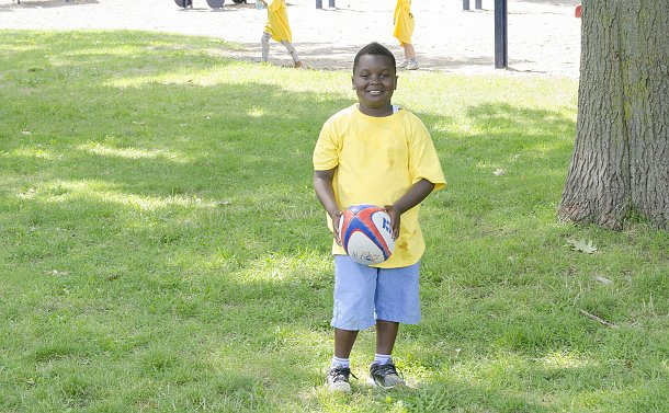 A boy holds a rugby ball