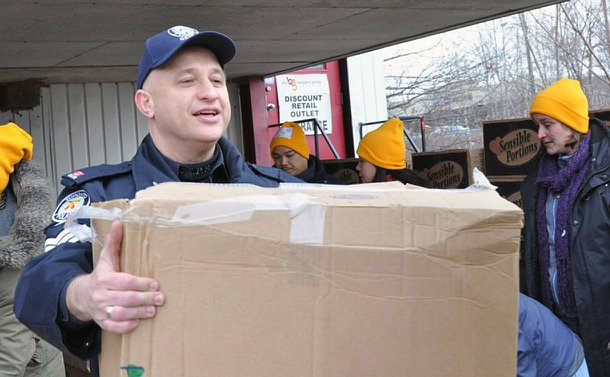 A man in Toronto Police uniform holding a large cardboard box