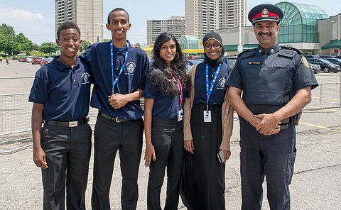 Four young people stand in a parking lot with an Police Inspector in uniform.