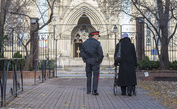 A police officer walks with a woman using a walker