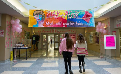 "A hallway with a banner reading ""day of pink"" as two students wearing pink walk underneath it."