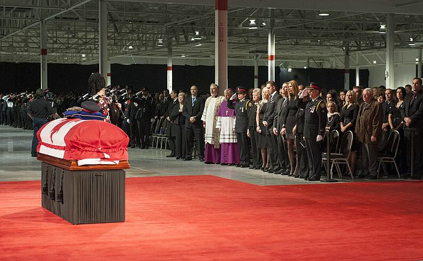 A casket in front of a large audience