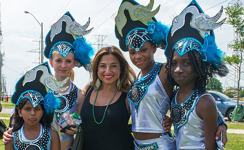 Four young girls in bright blue costumes pose with a female police constable.