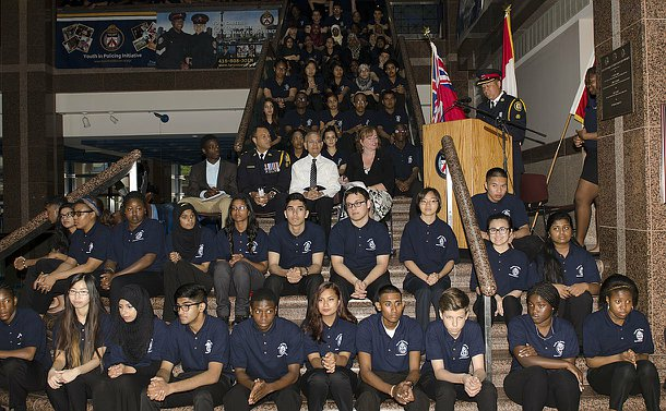 The 2014 Youth In Policing Initiative Intake Ceremony. The youth are sitting on the marble steps in the main area of the Toronto Police Service Headquarters.