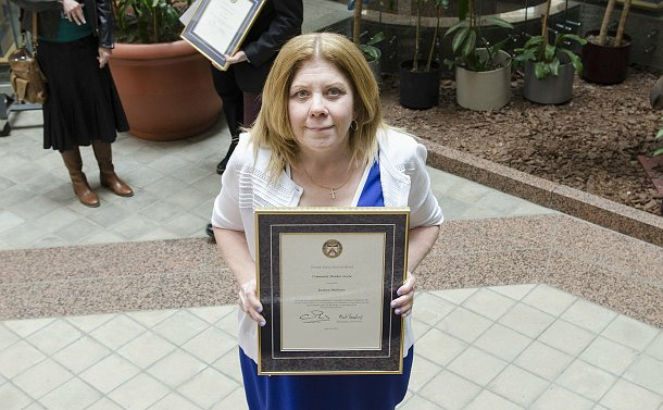 A woman holding a framed certificate