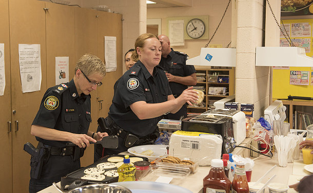 Two women in TPS uniform in a kitchen