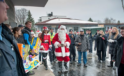 A crowd of people in a parking lot holding toys, with a man in a santa costume in the middle.