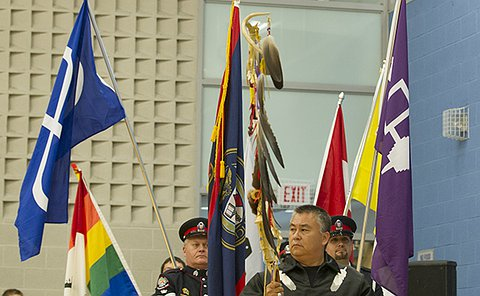 A man holds a large staff with large feathers attached to it followed by officers in TPS uniform carrying flags