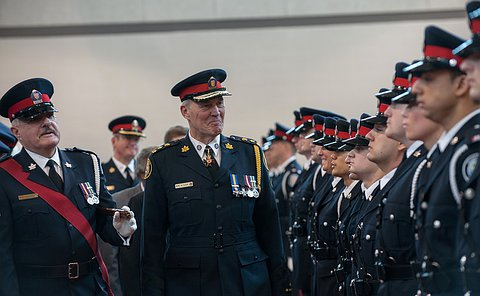 Chief william Blair smiling as he inspects cadets in dress uniform at their graduation.
