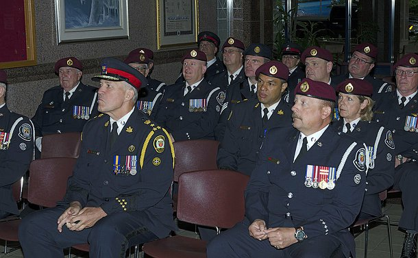 Group of officers sitting in the lobby of Toronto Police Headquarters during plaque unveiling