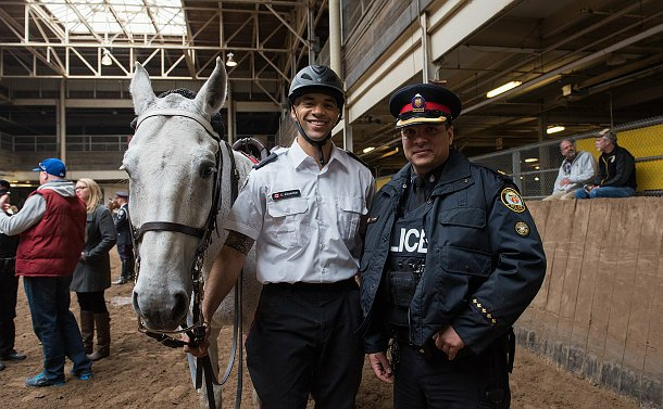 A man in mounted uniform next to an officer in regular TPS uniform