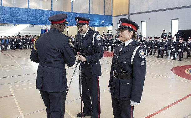 Two men in TPS uniform shake hands, one holding walking sticks, alongside a woman in TPS uniform