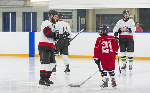 People in hockey uniform on a rink