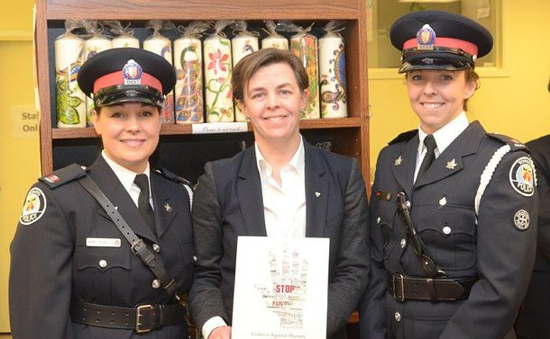 Two women in TPS uniform flanking another woman holding a book
