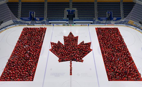 People wearing red standing over a Canadian flag on an ice rink