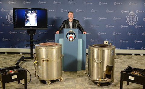 A man at a podium behind two large stainless steel cylinders and two smaller black pedestals