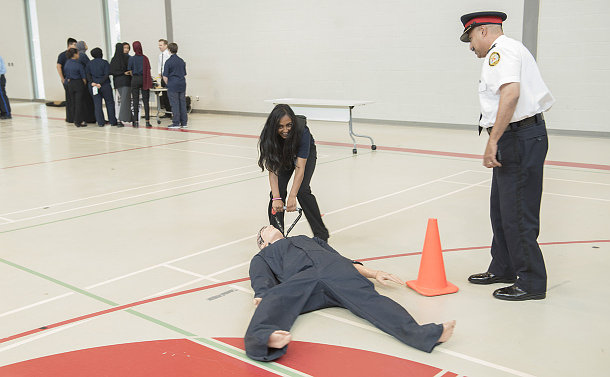 A man in TPS uniform beside a teenage girl pulling a dummy along a gym floor