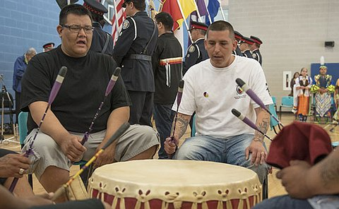 Two men sitting at a drum
