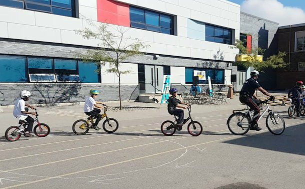 A man in TPS uniform on a bicycle followed by three children on bicycles
