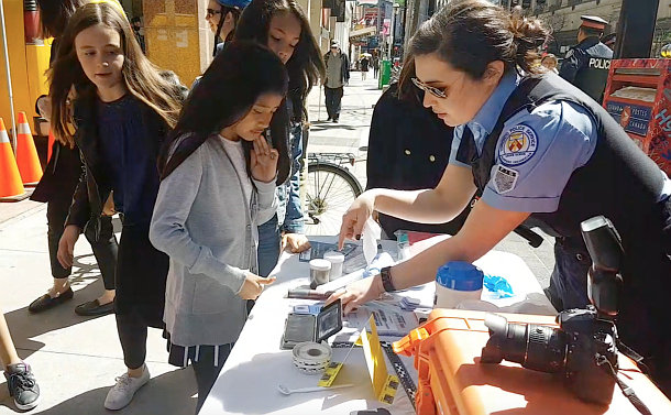 A woman in TPS civilian uniform shows items on a table to a girl