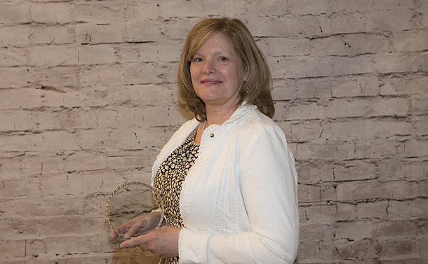 A woman holds a glass award
