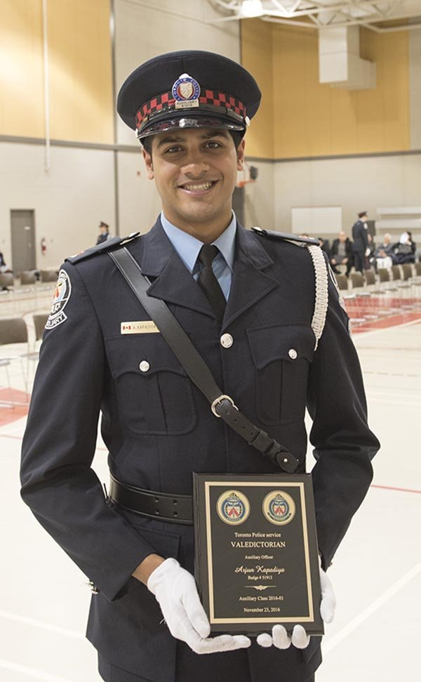 A man in TPS Auxiliary uniform holding a plaque