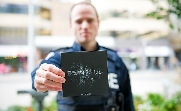 A man in TPS uniform holds a CD in front of him